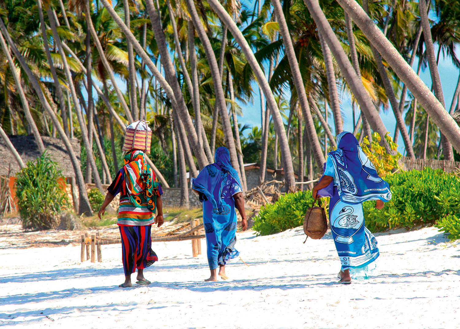 three tanzania women in traditional clothese walking along a beach
